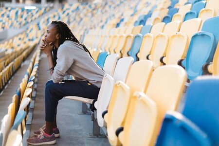 dreariness: Side view of sad african american young woman sitting waiting in rows of empty seats at stadium with her chin resting on hands and a glum expression. Stock Photo