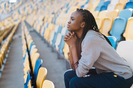 dreariness: Upset african american young womanin rows of empty seats at stadium with her chin resting on hands and a glum expression. Stock Photo