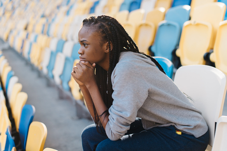 Side view of african american woman sitting with head on hands and feeling disappointed against stadium rows of seats .