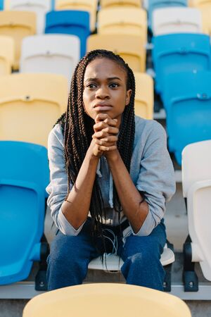 glum: Worried african american young woman sitting waiting in rows of empty seats in a stadium with her chin resting on her hands and a glum expression.
