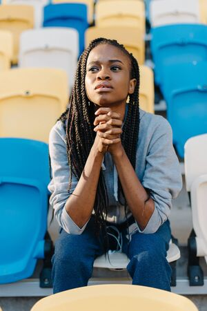 dreariness: Unhappy and frustrated african american woman sitting with her chin resting on hands and looking away.