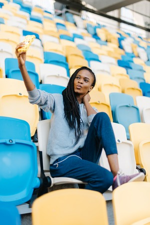 puckering lips: Beautiful sports african american woman with puckering lips making selfie photo on smartphone at stadium, plastic seats as background.