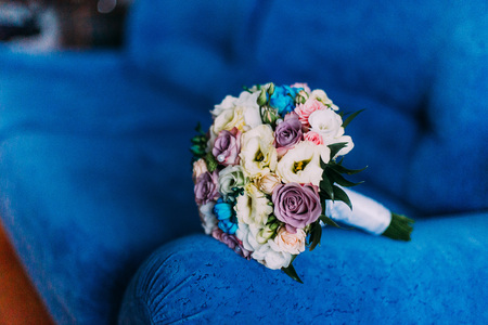 Beautiful bridal bouquet on blue sofa armrest. Wedding concept.