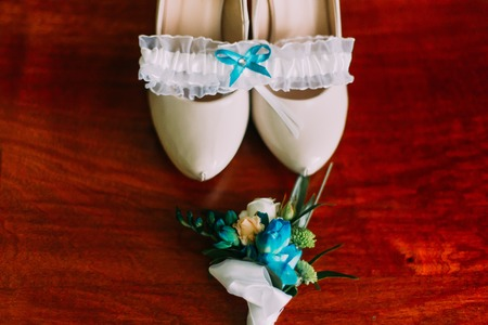 pureness: Close-up of cute brides wedding accessories - boutonniere, shoes and garter on wooden background. Stock Photo