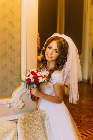 Smiling bride in wedding dress holding a cute bouquet with red and white roses posing on background of vintage wooden interior. Stock Photo