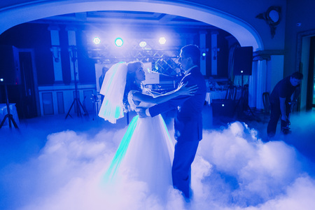 fume: First dance of newlywed couple. The hall is covered with white fume and filled by blue lights. Stock Photo