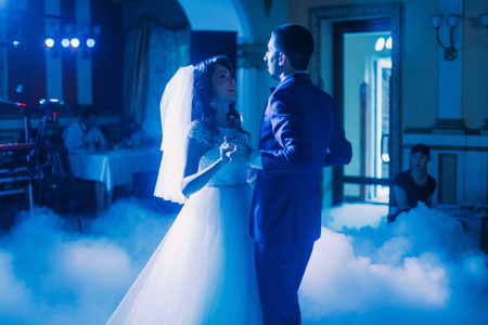 fume: First wedding dance of newlywed couple. The hall is covered with white fume and filled by blue lights. Stock Photo