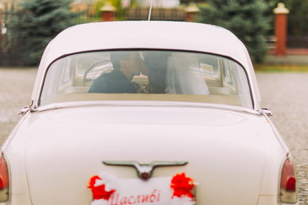 Happy newlywed couple kissing on a backseat of retro car, rear view.
