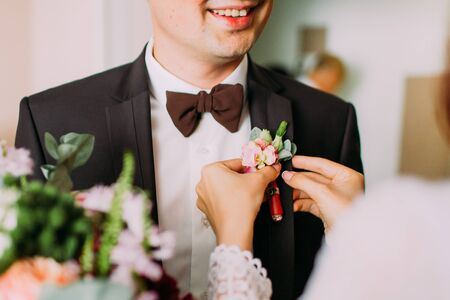 bilding: Delicte brides hands pin pink and violet boutonniere to grooms tuxedo. Stock Photo