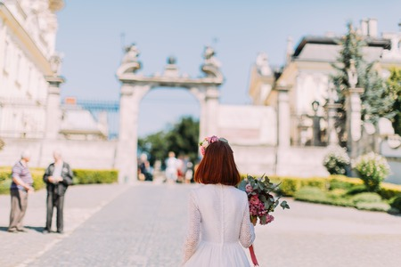 view from behind: Gorgeous stylish red headed bride in vintage white dress walking in old city, view from behind.