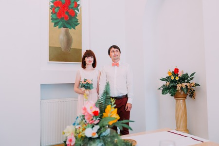 affable: Bappy bride and groom at marriage registration office. Cute red haired woman with a bouquet of flowers in hands. Stock Photo