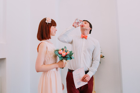 Happy newlyweds on their wedding ceremony in registration office drinking wine and celebrating. Stock Photo
