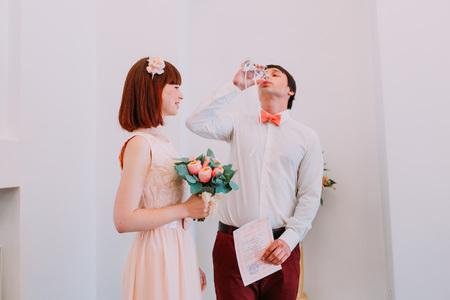registro: los recién casados ??felices en su ceremonia de boda en la oficina de registro de beber vino y celebrando. Foto de archivo