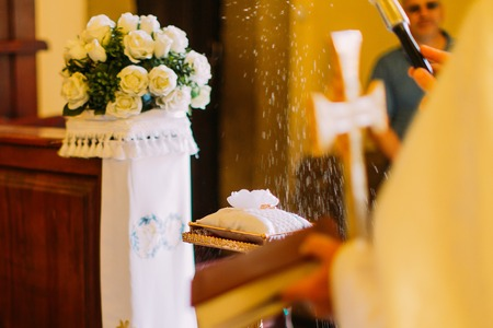 baptizing: Priest baptizing wedding rings on cute white pillow with holy water at ceremony. Stock Photo