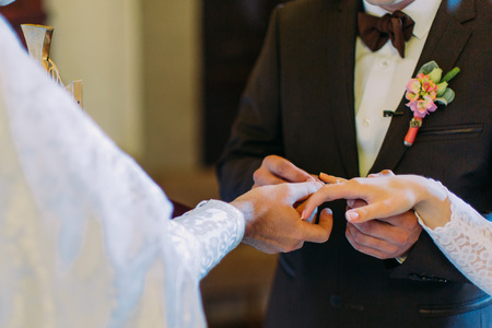 glans: Priest is putting the ring on brides finger during orthodox wedding ceremony.