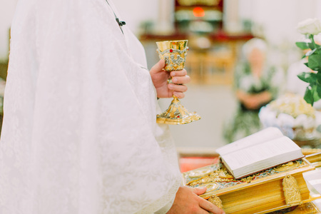 Priest hands during open air mass, Bible and cup of wine on the sacred cloth.