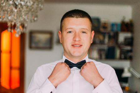 wrist cuffs: Elegant young fashion man in white shirt dressing bow-tie. Close-up.