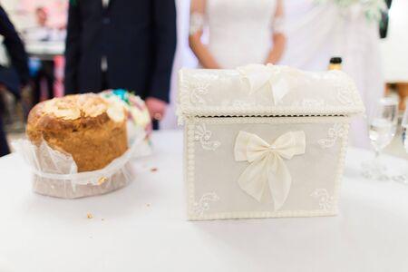 Hochzeitskasten für Wünsche und Geld zusammen mit traditionellem Brot auf Tabelle an der Feier.
