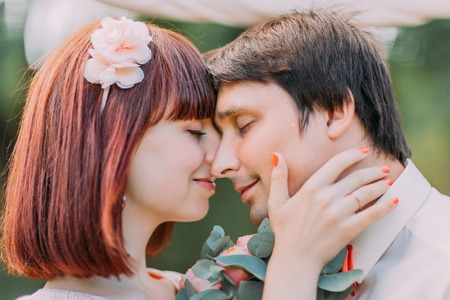 touching noses: Happy smiling bride holding grooms head tende, touching each other noses with closed eyes. Stock Photo