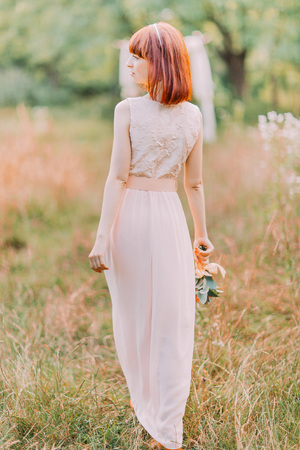 view from behind: Beautiful bride wearing beige dress with skirt-paced looking away walking in the Park, view from behind.