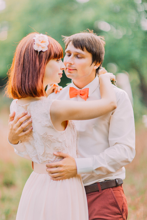 Man holds brides waist tenderly at the background of green forest, she holds hand on his shoulders.