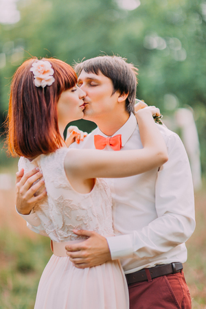 misterious: Groom kisses bride tenderly holding her waist while they stand in the park.
