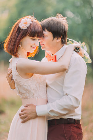 Handsome groom holds brides waist tenderly standing in the middle of forest meadow. Stock Photo