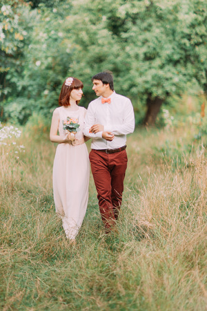 happy moment: Happy newlywed bride and groom walking holding hands in the summer forest. Woman with red hair. Happy moment.