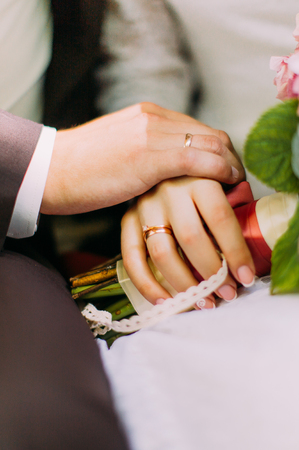 Closeup of bride and groom showing wedding rings touching hands with bridal bouquet.