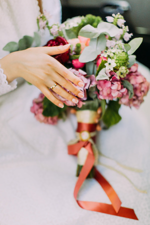 Beautiful summer wedding bouquet in hand with ring of the bride.