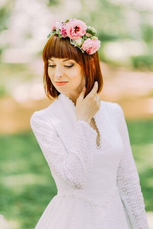 Modern and stylish red-haired bride in a floral wreath on her head looking down outdoors.
