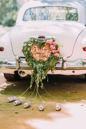 Vintage bruiloft auto met enkel gehuwd teken en blikjes gehecht, close-up.