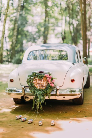 attached: Bumper of retro car with just married sign and cans attached.