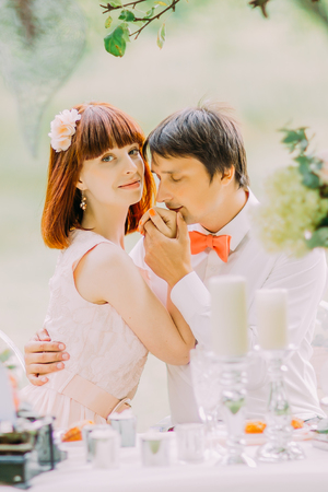 Wedding photograph of a young couple who are just married and celebrating on picnic with champagne, groom kissing brides hand Stock Photo