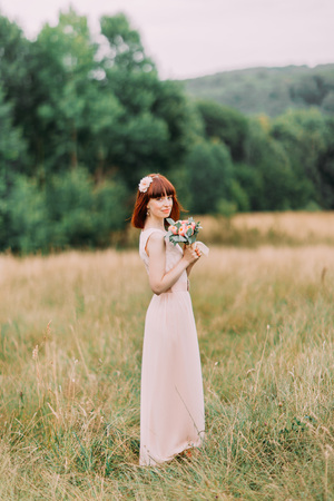Full-length of sensual red-haired bride in pink dress standing on meadow with bouquet.