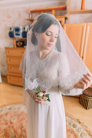 Close-up portrait of beautiful bride in wedding dress with veil posing indoors in dressing room. Stock Photo