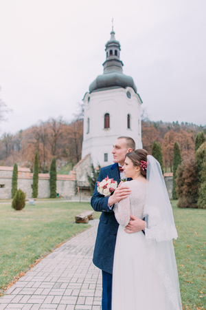 Handsome groom tenderly embracing his new wife in green park of old monastery. Stock Photo