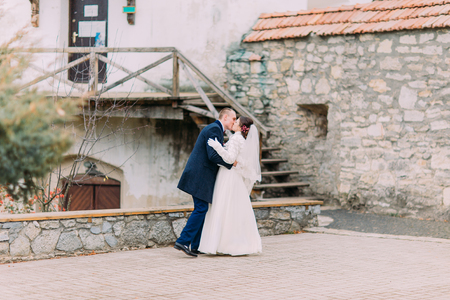 passionate kissing: Romantic and passionate newlywed couple kissing on backround of ancient castle fortifications. Stock Photo