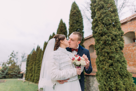 fortified wall: Handsome groom tenderly kissing his elegant new wife near cypress trees and fortified wall in romantic park.