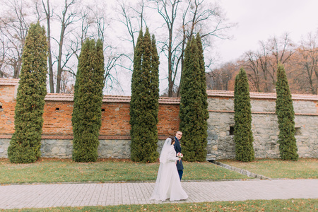 fortified wall: Handsome groom posing with his wife near cypress tree row and fortified wall as background in romantic park. Stock Photo