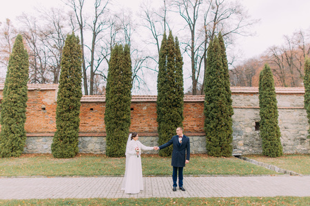 fortified wall: Handsome groom posing with his wife near cypress trees and fortified wall in romantic park.