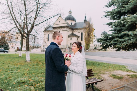 sensually: Panoramic view of beaytiful newlywed couple sensually holding hands in park near old baroque church.