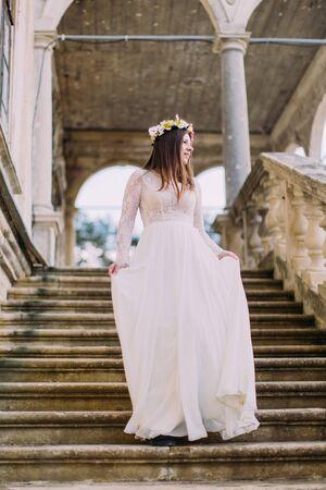 bajando escaleras: Casa de la novia de vestido blanco largo y la corona de flores que va abajo por las escaleras de piedra antiguos.