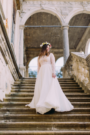 bajando escaleras: Charming bride in long white wedding dress and floral wreath going down by antique palace stone stairs. Foto de archivo