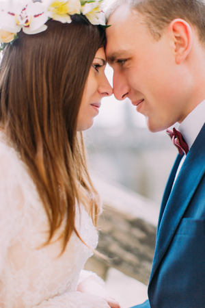 Beautiful newlywed bride and groom sensually touching foreheads in silent owe of belonging. Stock Photo