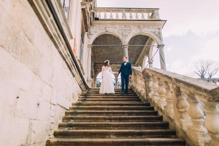 bajando escaleras: El novio apacible que sostiene las manos al ir abajo con su novia bonita por las escaleras antiguas de la piedra del palacio. Tiro de ángulo bajo. Foto de archivo