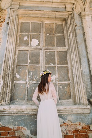 innocent: Tender innocent bride stands in front of ruined window at ancient abandoned palace.