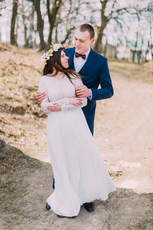 Wedding portrait of happy stylish newlywed bride and groom posing outdoor with leafless trees at background.