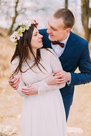 fiancee: Wedding portrait of happy stylish newlywed bride and groom posing in spring park.