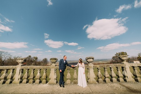 Wedding portrait of happy stylish newlywed bride and groom posing at old stone terrace in spring park with amazing clouded sky as background. Stock Photo
